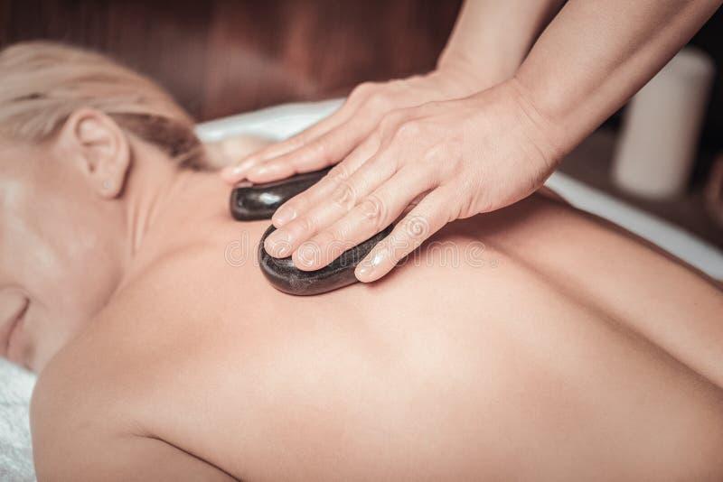 De deskundige masseuse die van Nice hete stenen voor massage gebruiken stock afbeelding