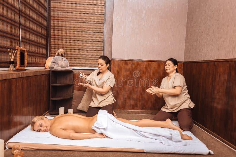 De deskundige masseusen die van Nice voor de massage voorbereidingen treffen stock afbeelding