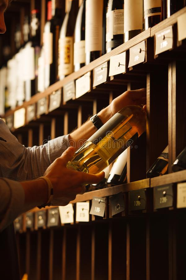 De deskundige in wijnbereiding kiest elite witte wijn in kelder stock afbeeldingen