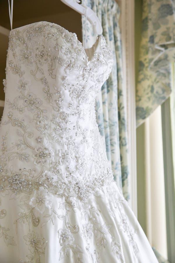 De details van een wit huwelijk kleden het hangen in een ruimte wachtend op een bruid stock afbeelding
