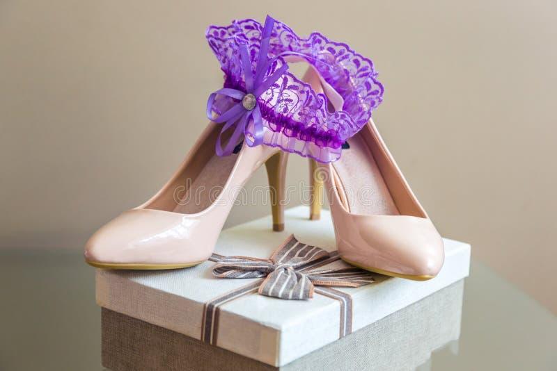 De details van het huwelijk Purpere Kouseband op Bruid` s Pantoffels Doos met een gift stock fotografie