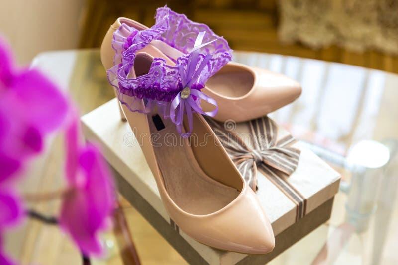 De details van het huwelijk Purpere Kouseband op Bruid` s Pantoffels Doos met een gift stock foto