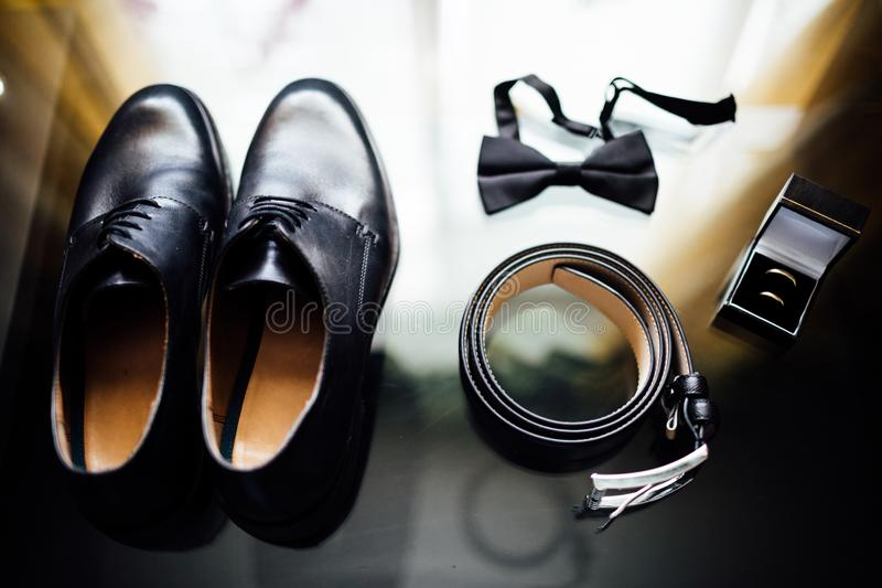 De details van het huwelijk De toebehoren van de bruidegom Schoenen, ringen, riem, en bowt stock afbeelding