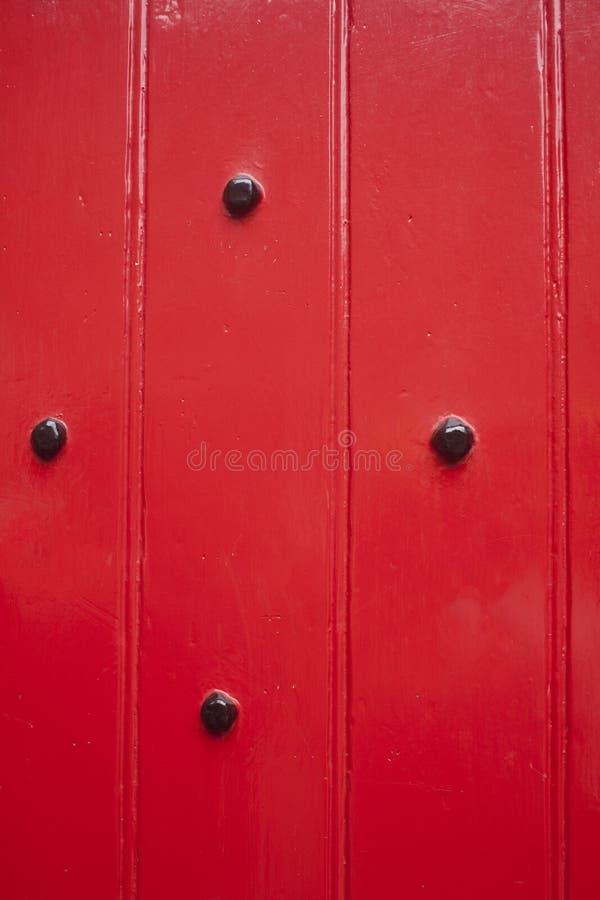 De deur schilderde rode en zwarte ornamentenspijkers stock fotografie