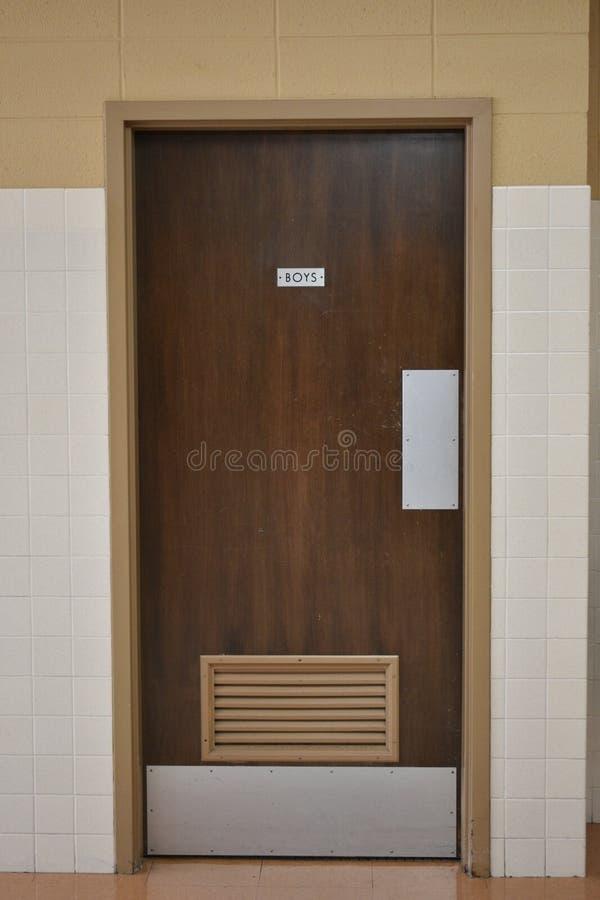 De deur van de jongensbadkamers in een retro schoolkerk royalty-vrije stock foto