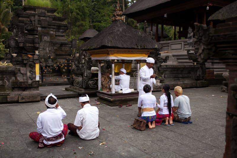 24 DE DEZEMBRO DE 2017 - BALI, INDONÉSIA: A cerimônia de devotos hindu reza no templo de Tirta Empul conduzido por um suco-sacerd imagens de stock