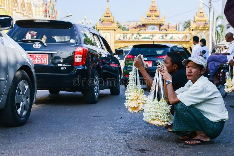 16 de dezembro de 2016 povos de myanmar que vendem a flor para o dinheiro na rua quando engarrafamento na cidade de yangon, myanm fotografia de stock royalty free