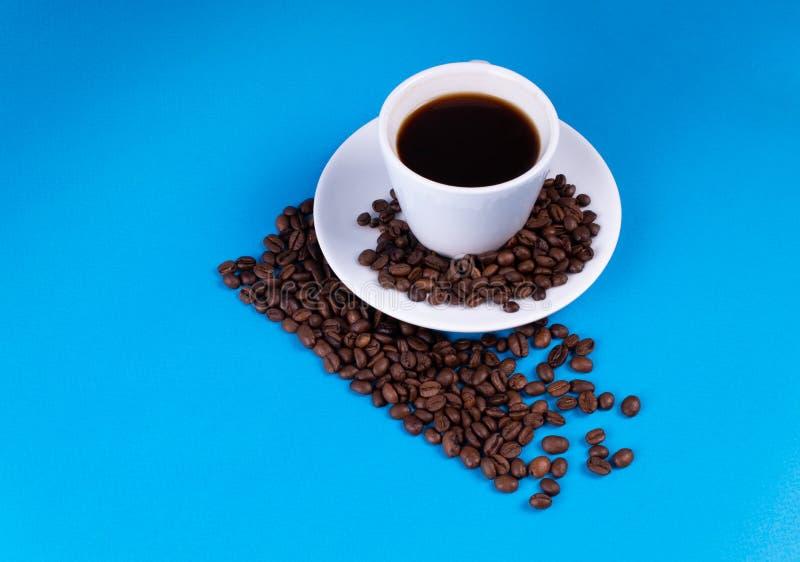 De diagonale lijn wordt gemaakt van koffiebonen; een kop met een schotel wordt gevuld met koffie over de lijn royalty-vrije stock foto's