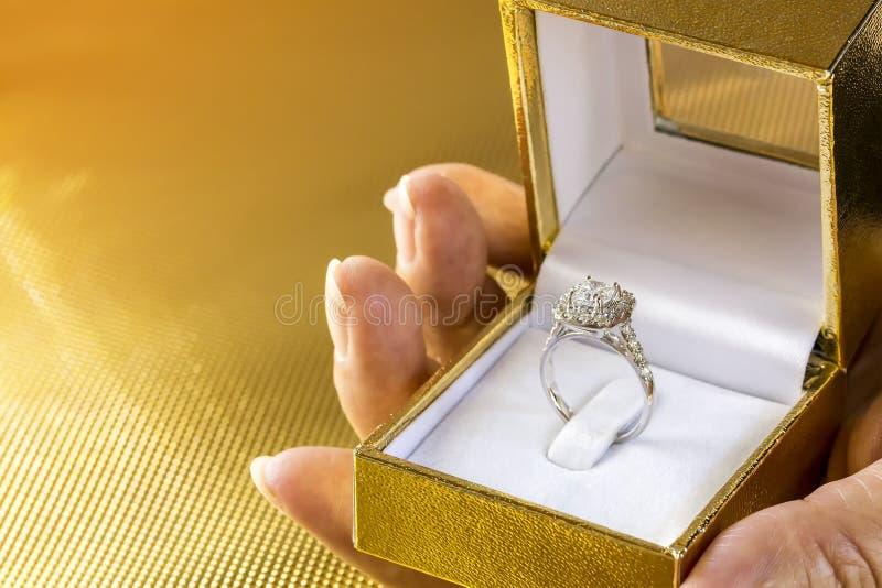 De diamantring van het mooie en luxehuwelijk in vakje op vrouwenhand op gouden achtergrond met exemplaarruimte stock afbeeldingen