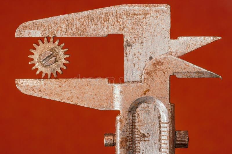 De diameter van een tandrad wordt gemeten met een roestige beugel stock afbeeldingen