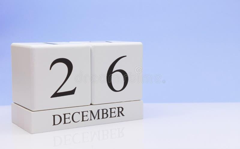 26 de diciembre día 26 del mes, calendario diario en la tabla blanca con la reflexión, con el fondo azul claro Invierno, vacío imagen de archivo libre de regalías