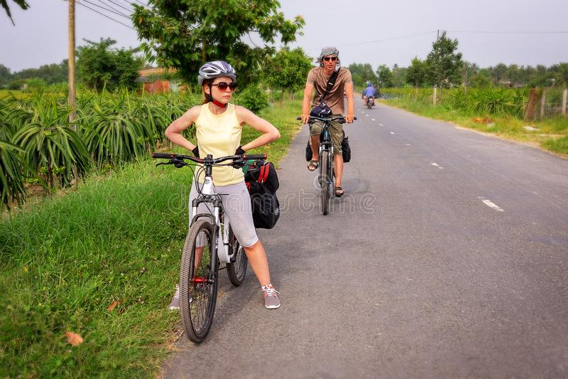28 DE DICIEMBRE DE 2016, Vietnam, puede Txo Dos viajeros en las bicicletas Turismo vietnamita Delta del Mekong entre campos del a imagen de archivo