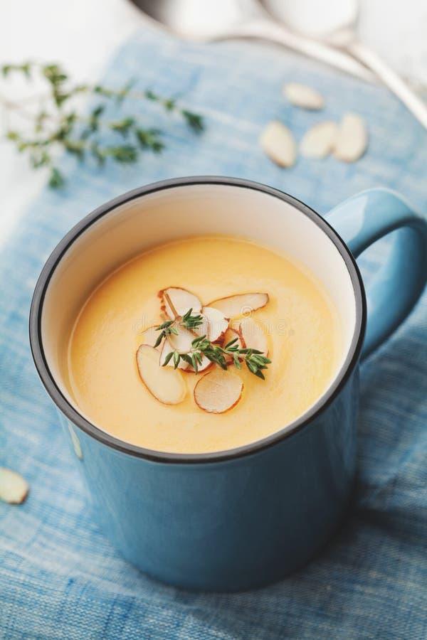 De dieet plantaardige roomsoep van wortel en aardappel verfraaide amandelenvlokken in blauwe kom op linnenservet stock afbeelding
