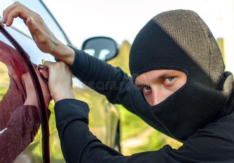 De dief breekt de deur in de auto stock fotografie