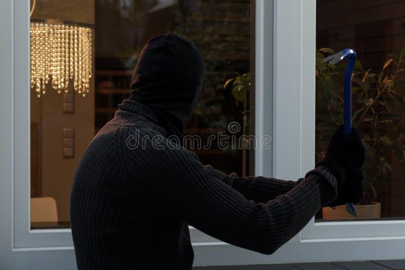 De dief breekt het glas stock foto