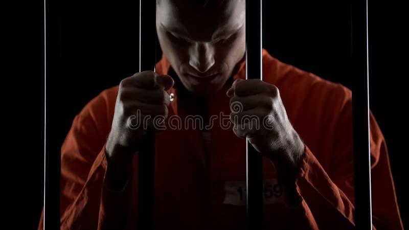 De dief in gevangenis oprecht voelen betreurt van misdaad, die gevangenisbars in wanhopig houden royalty-vrije stock foto