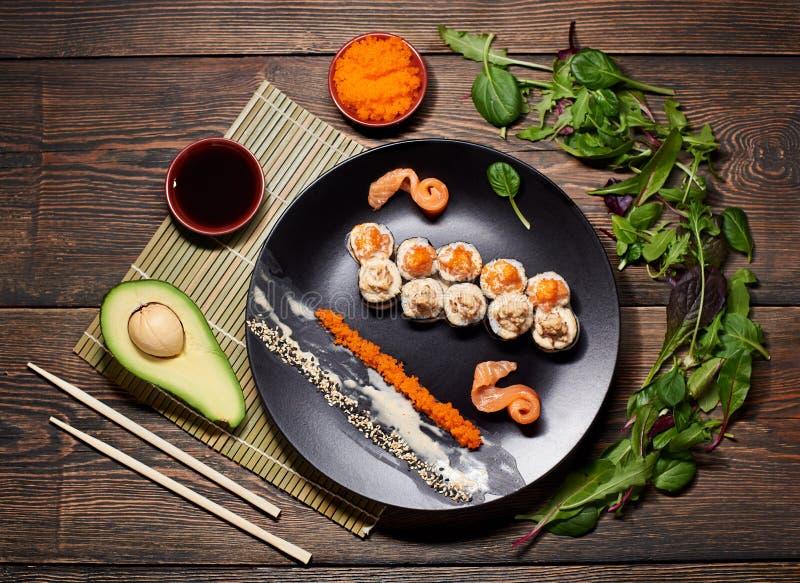 De dienende sushi rolt en ander traditioneel Japans en Aziatisch voedsel op een lijst stock foto's