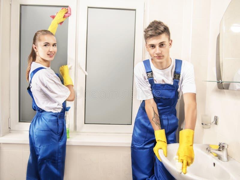 De dienst die het venster en de wasbak schoonmaken die binnenshuis glimlachen stock afbeelding