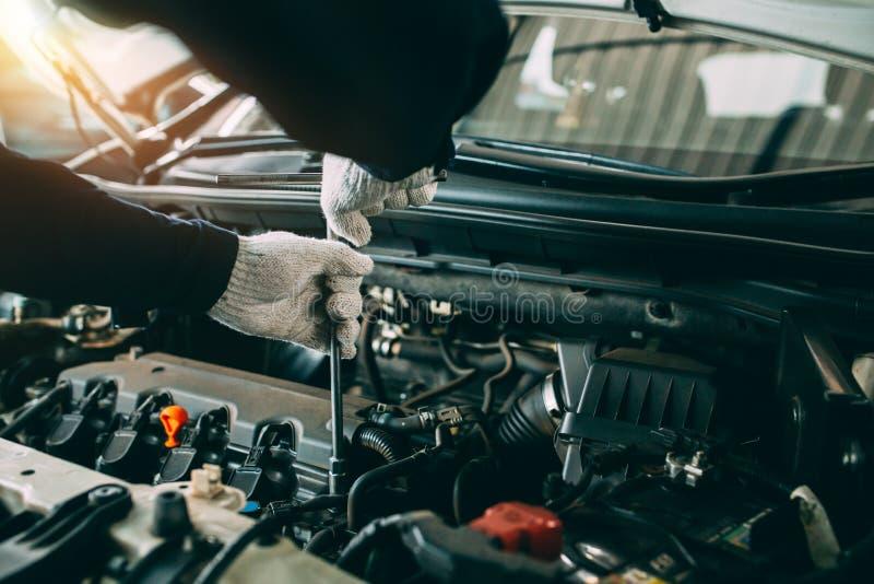 De dienst van de autoreparatie, het Auto mechanische werken in garage, Mechanische handen die van nut van de auto in open kap con stock foto