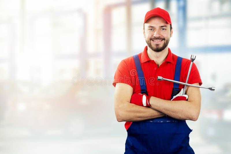 De dienst van de autoreparatie - autowerktuigkundige met in hand moersleutel stock afbeelding