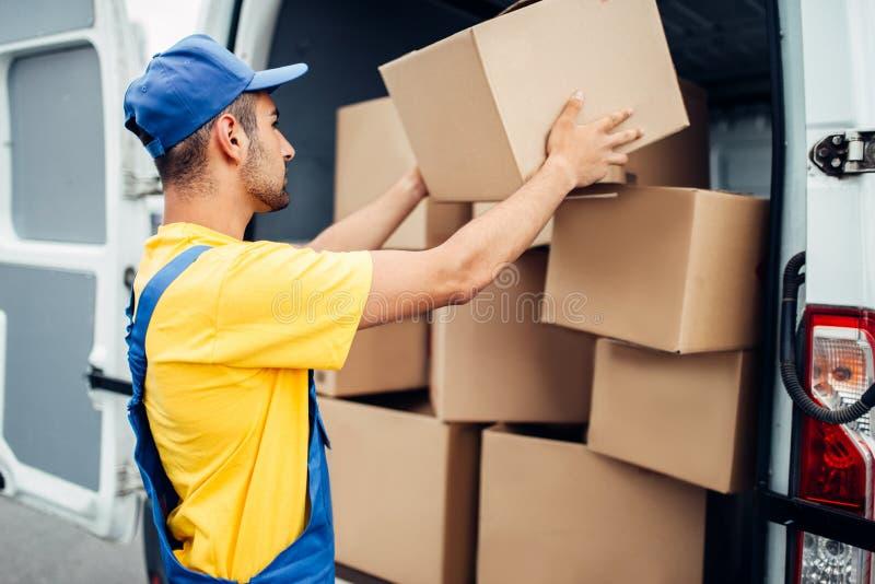 De dienst van de ladingslevering, mannelijke koerier maakt vrachtwagen leeg royalty-vrije stock foto