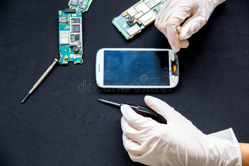 De dienst van de elektronikareparatie - de technicus bevestigt gebroken celtelefoon stock afbeeldingen