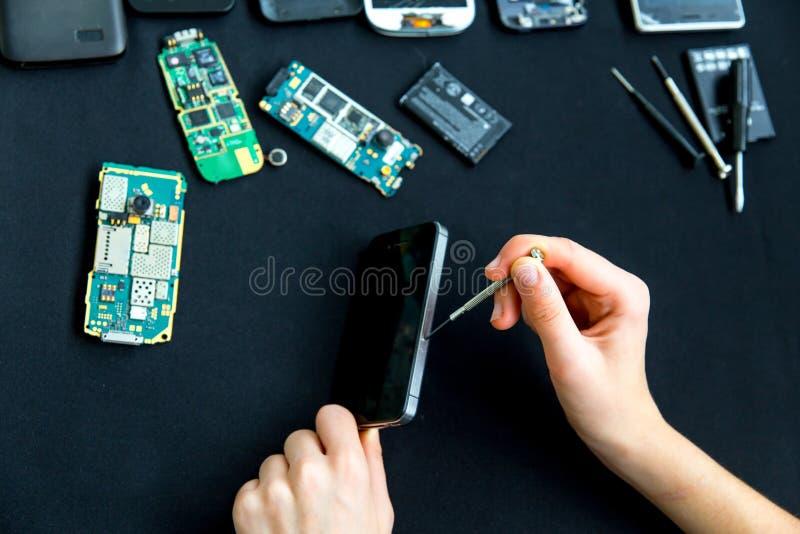 De dienst van de elektronikareparatie - de technicus bevestigt gebroken celtelefoon stock foto