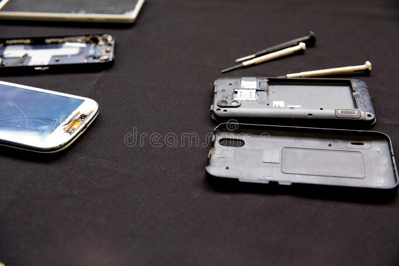 De dienst van de elektronikareparatie - de technicus bevestigt gebroken celtelefoon royalty-vrije stock afbeelding