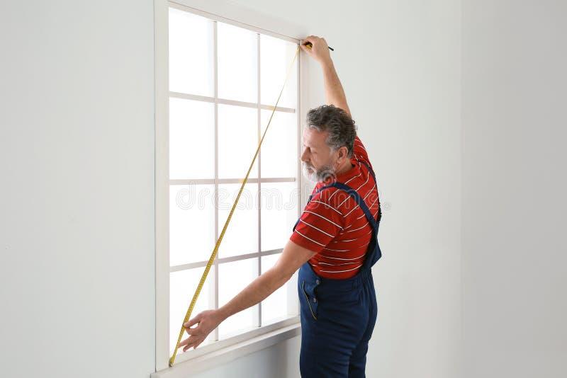 De dienstmens die venster voor installatie binnen meten royalty-vrije stock fotografie