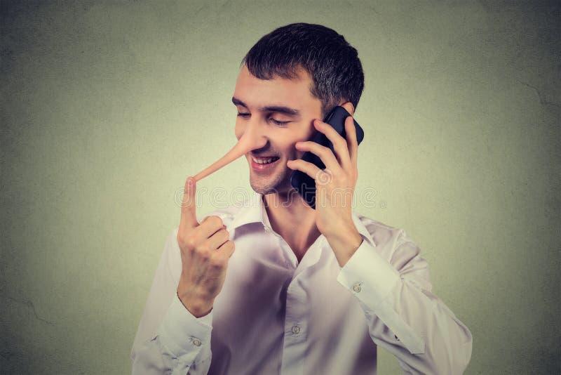 De dienstvertegenwoordiger van de leugenaarklant Gelukkige mens met lange neus die op mobiele telefoon spreken stock fotografie