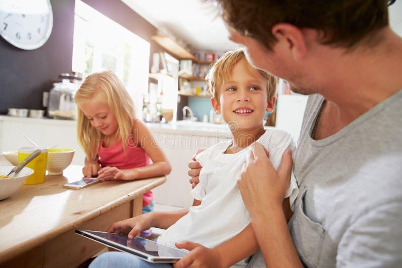 De Digitale Apparaten van vaderand children using bij Ontbijtlijst stock afbeeldingen