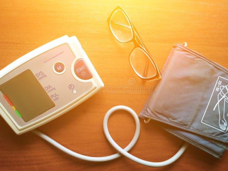 De digitale de bloeddrukmaat en glazen zijn op de bruine achtergrond royalty-vrije stock foto