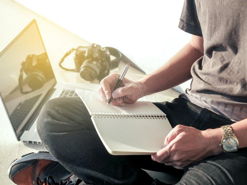 De digitale blog van de mensenlevensstijl schrijft pen op notitieboekje en werkt aan laptop, ontspant een mens het werken van hui stock foto