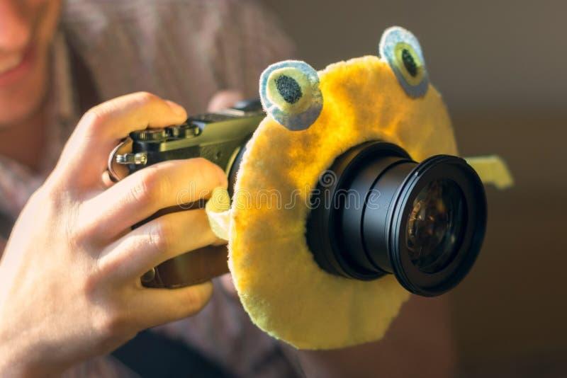 De digitale DSLR-camera in een hand met een stuk speelgoed van kinderen op de cameralens om de aandacht van het kind aan te trekk stock foto's