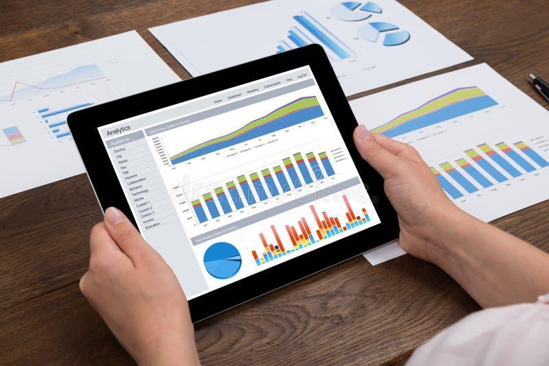 De Digitale Tablet van Person Analyzing Financial Statistics On royalty-vrije stock foto