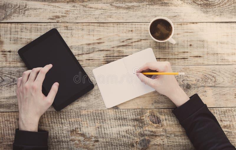 De digitale tabletcomputer in mannetje overhandigt koffieachtergrond - dien houten plancs, kop van in koffie, nootbook, potlood S stock foto's