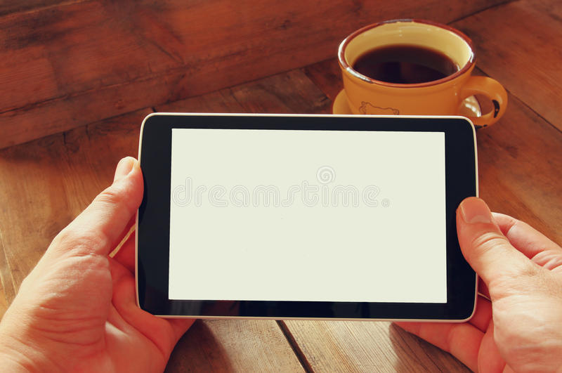 De digitale tabletcomputer met het geïsoleerde scherm in mannetje overhandigt houten lijstachtergrond en kop van koffie stock foto
