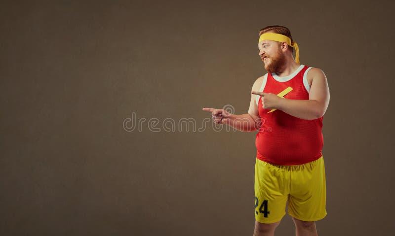 De dikke grappige mens in sporten kleedt punten met zijn vinger royalty-vrije stock afbeelding
