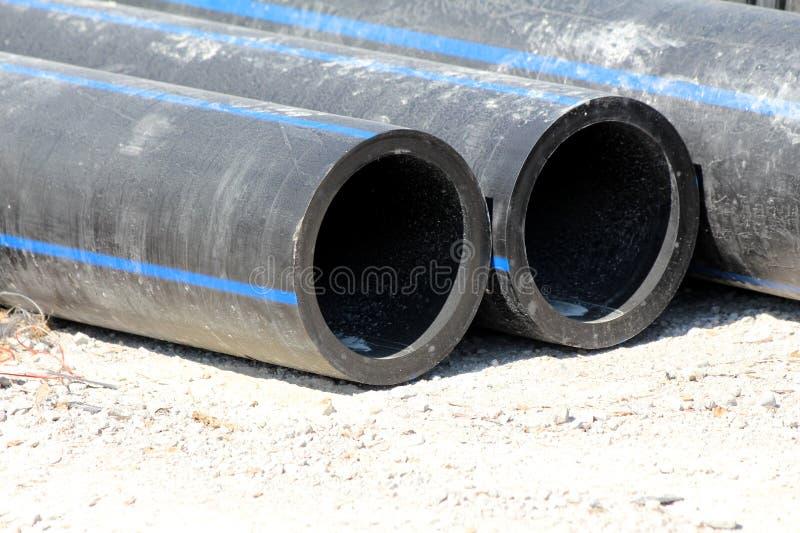 De dikke zwarte rubberpijpen gingen op grintweg weg bij lokaal te installeren bouwwerfwachten stock afbeelding