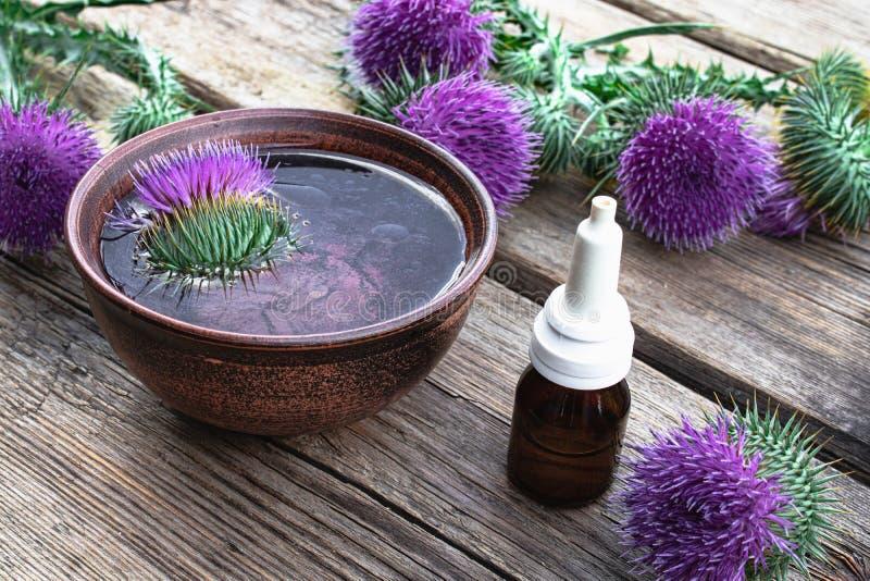 De disteletherische olie in een fles op de lijst dichtbij de distel bloeit op houten achtergrond stock foto's