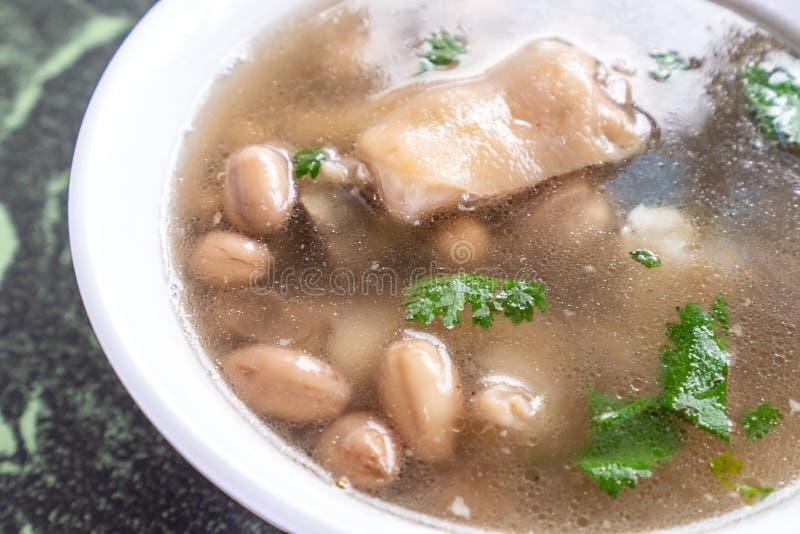 De distinctieve beroemde snacks van Taiwan ` s: De draversoep van het pindavarkensvlees knucklepig ` s in een witte kom op steenl royalty-vrije stock afbeelding