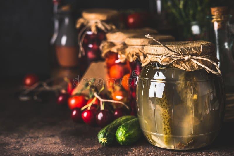 De diverse bewaarde vergiste seizoengebonden groenten en vruchten van tuin in glaskruiken op donkere rustieke achtergrond, sluite royalty-vrije stock foto's