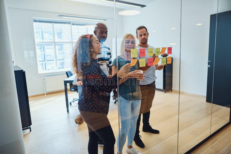 De diverse brainstorming van het ontwerpteam met kleverige nota's in een bureau stock afbeeldingen