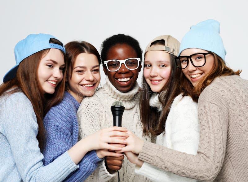 De diverse multinatiemeisjes groeperen zich, tiener vrolijk vriendenbedrijf die pret met microfoon hebben royalty-vrije stock afbeelding