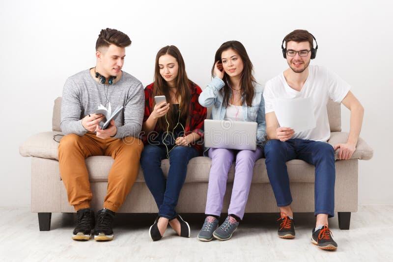 De diverse studenten die gadgets gebruiken, zitten op bank stock fotografie