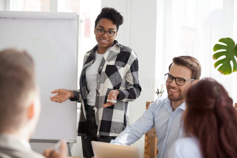 De diverse werknemers lachen tijdens flipchartpresentatie bij vergadering stock afbeelding