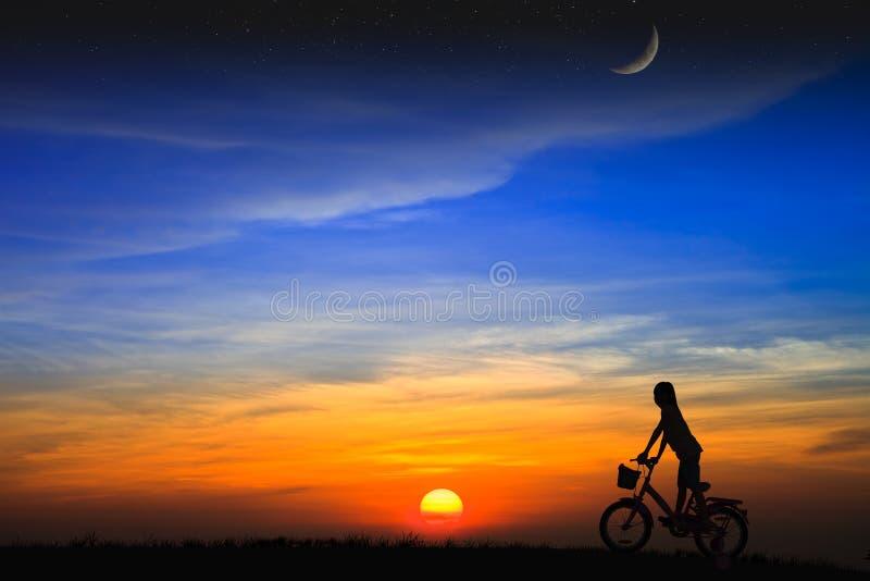 De dochter die van het silhouet een fiets berijden op de zonsondergang royalty-vrije stock afbeeldingen