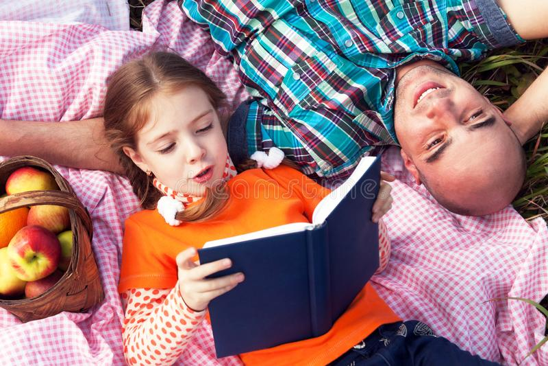 De dochter en de vader lezen het liggen op het gazon op een grasrijke zonnige dag stock fotografie