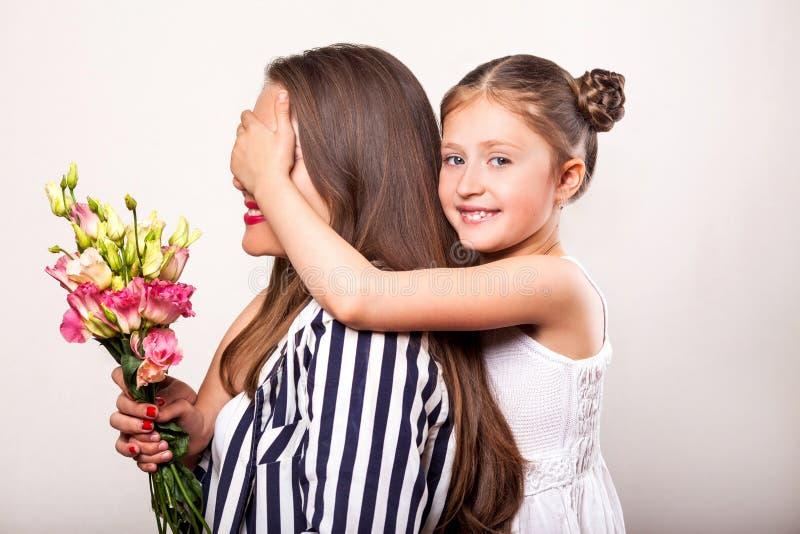De dochter geeft bloemen aan haar moeder op haar moeder` s dag stock afbeelding