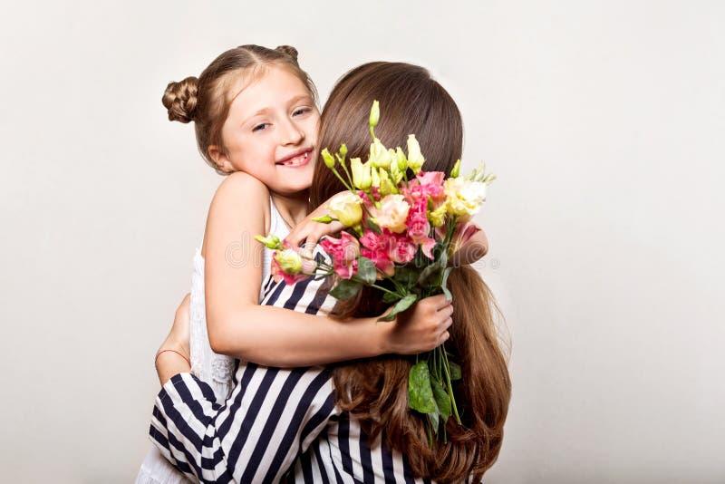 De dochter geeft bloemen aan haar moeder op haar moeder` s dag stock foto's